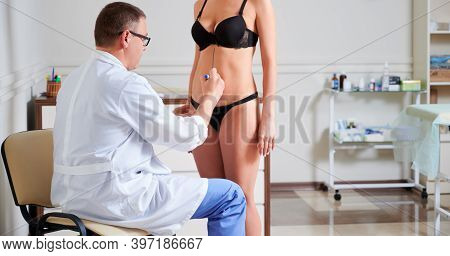 Male Doctor Drawing Marks On Female Body Before Plastic Surgery. Woman Standing In Front Of Surgeon