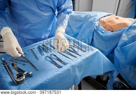 Close Up Of Surgeon In Sterile Gloves Getting Ready Medical Instruments. Female Patient With Marks O