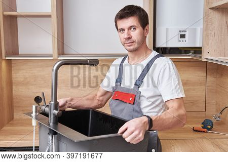 Male Plumber Installs A Sink In The Kitchen