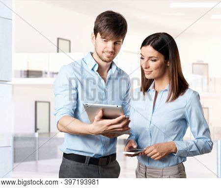 Business partners working. Young business people in office. Businessman and businesswoman working with tablet and phone.