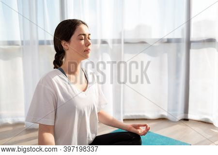 A Young Pretty Woman Meditates On A Sports Mat, Closed Her Eyes. A Room In The Sunlight. The Concept