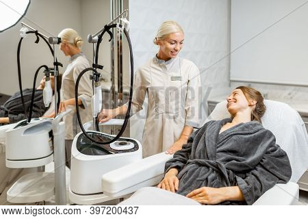 Young Woman Client With A Doctor During A Facial Rejuvenation Treatment At Medical Spa Office. Conce