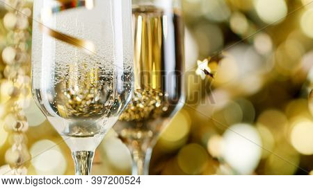 Pair of Champagne Flutes with Bubbles on Golden Light Background, Close-up.