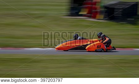 A Panning Shot Of A Racing Sidecar As It Corners On A Track.