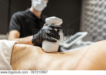 Man During An Ultrasound Liposuction Procedure At Luxury Spa Salon. Doctor Working On Waist Side Are