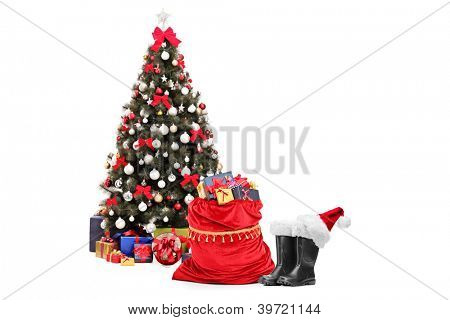 Christmas tree amd santa accessories, pair of boots and bag full of presents isolated against white background