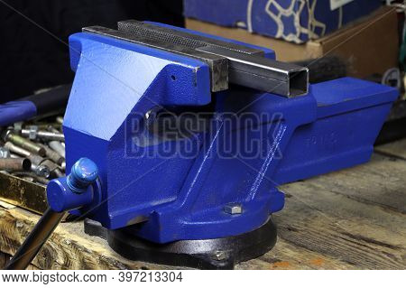 Blue Vise On A Wooden Table. Bench Tools. Vice
