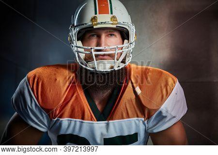 Portrait of american football player in helmet, looking dedicated.