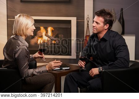 Happy business people meeting in hotel lobby talking and drinking wine - at fireplace in business club.