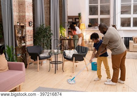 Young father of African ethnicity showing his little son how to wash the floor in living-room while mother and daughter cleaning table together