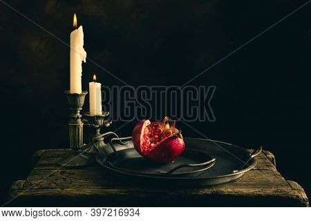 Still life on wooden table with antique plates and a pomegranate cut open.