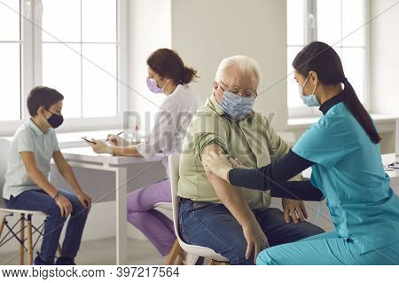 Nurses Giving Flu Shots To Older Adults And Children During Vaccination Campaign
