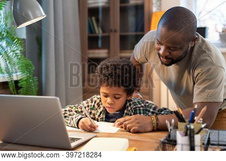 African schoolboy in casualwear making notes in copybook while his father bending over table, pointing at page and explaining something to him