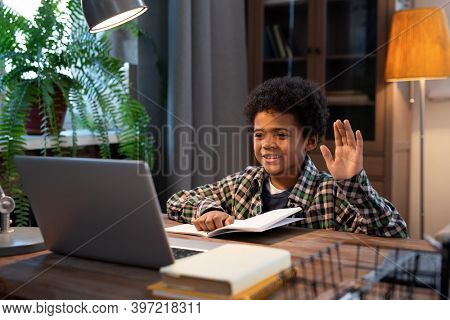 Cute little African schoolboy in casualwear waving hand to someone while sitting by table in front of laptop and communicating in video chat