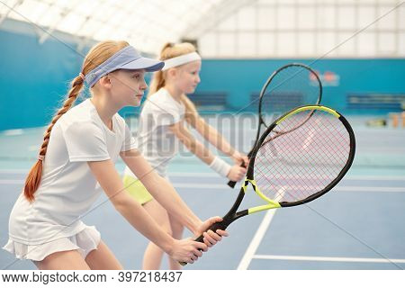 Two teenage girls in activewear standing on stadium with their legs bent in knees and holding tennis rackets ready to push the ball during play
