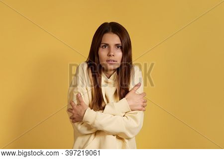 Clatter With Teeth. Desperate Caucasian Woman In Yellow Hoodie Trembles And Feels Cold, Huggs Hersel