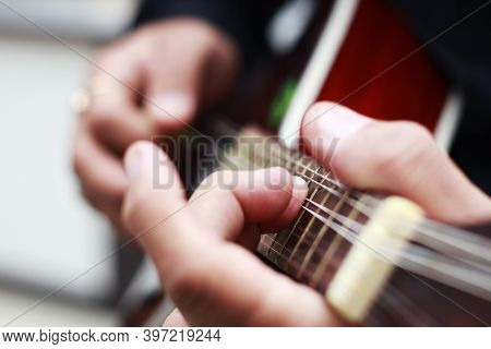 Hands Of Musician Playing Mandolin With Selective Focus On Front Fingers- Hands Of Musician Playing