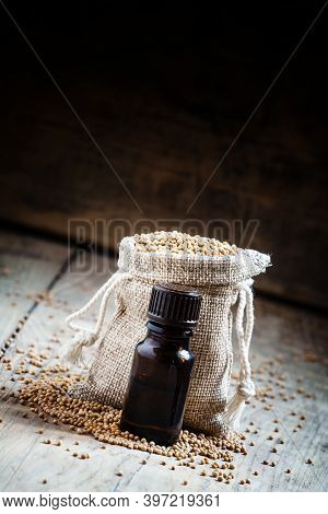 Essential Oil Of Mustard In A Small Brown Glass Bottle, And Mustard Seeds In A Bag Of Sackcloth On T