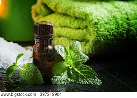 Peppermint Essential Oil In A Spa Concept With Towel, Sea Salt, Aromatic Candles On A Dark Wet Backg