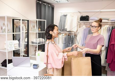 Happy young female shop assistant passing big paperbags with new clothes to elegant Asian customer after payment for purchase