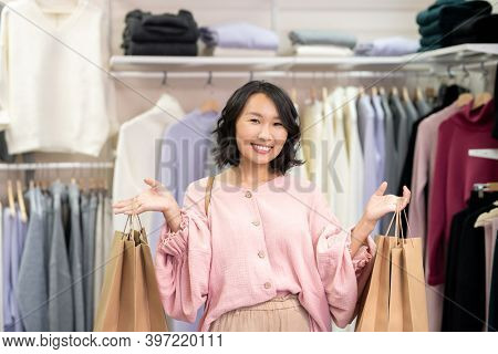 Young cheerful female shopaholic in smart casualwear holding two packs of big paperbags with purchases while standing in clothing department