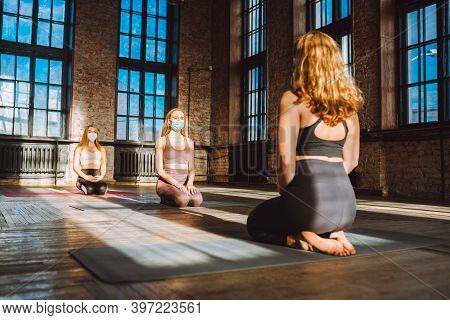 Group Of Women Practicing Yoga In Big Loft Style Class Wearing Protective Medical Face Masks. Pandem