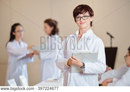 Pretty Positive Young Doctor In Labcoat Standing With Clipboard In Hands, Her Collagues Talking In B