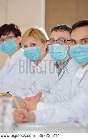 Group Of Pharmacologists In Medical Masks Attending Conference On Health Service Problems