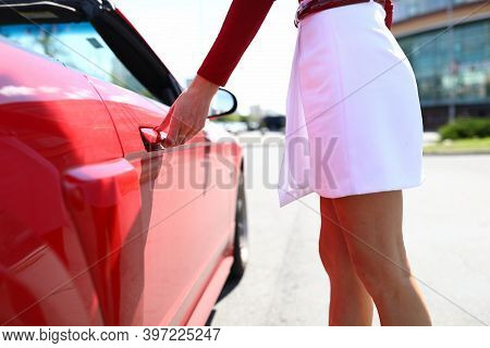 Woman In White Skirt Opens The Door Of Red Car. Car Service Concept