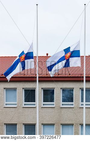 Two Finnish Flags Lowered To Half Mast On The Occasion Of Mourning At Cloudy Autumn Day