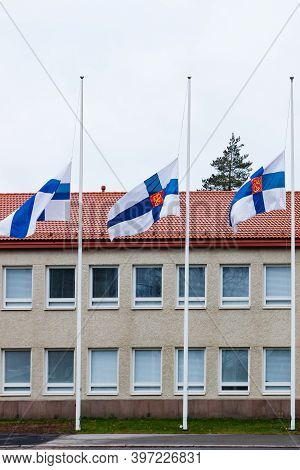 Three Finnish Flags Lowered To Half Mast On The Occasion Of Mourning At Cloudy Autumn Day