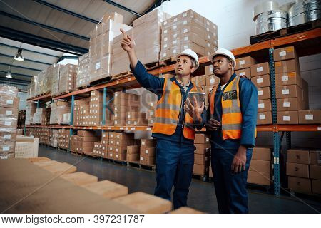 Factory Engineers Examining Their Stock At Manufacturing Storehouse With Digital Tablet