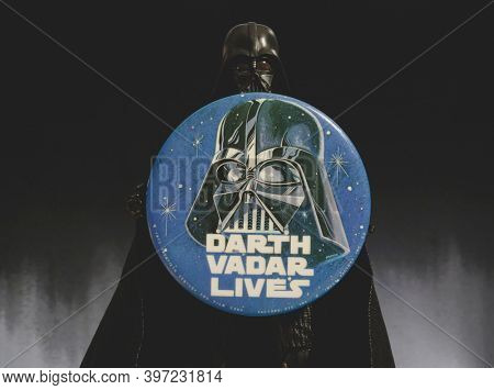 NOV 28 2020: Darth Vader action figure holds a Darth Vader Lives vintage button, spelled Vadar, in memory of actor David Prowse who passed away