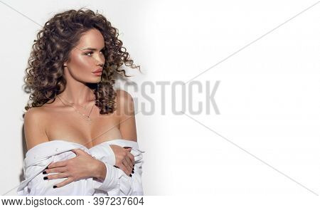 Beautiful young woman with curly hair posing, beauty model portrait, closeup. Beautiful sexy model girl in white cotton shirt. Flying hair, perfect make-up and Hairstyle.