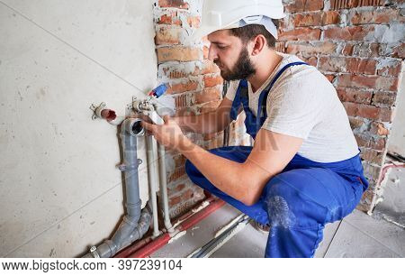 Young Plumber, Wearing Blue Uniform And White Helmet Working With Sealant Fix Of Sewer Pipe In Kitch