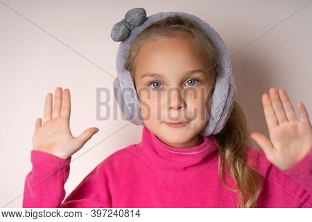 Little Cute Girl Raised Two Palms Up And Looks At The Camera, She Is In Warm Fur Headphones On A Lig