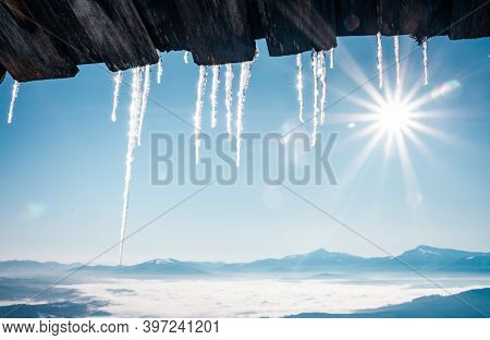Spectacular icicles shine in sun against blue sky. Splendid view with ice icicles hanging from roof of house. Location place Carpathian mountains, Ukraine, Europe. Happy New Year! Beauty of earth.