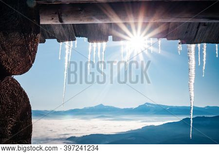 Spectacular icicles shine in sun against blue sky. Splendid view with ice icicles hanging from roof of house. Christmas holiday concept. Vibrant photo wallpaper. Happy New Year! Beauty of earth.