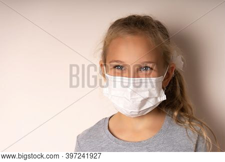 Little Blonde Girl Wearing A Medical Mask
