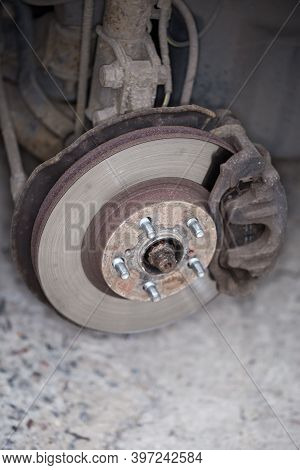 Front Strut, Wheel Hub And Disc Brake Assembly On An Used Car, View With Removed Wheel Close-up In S