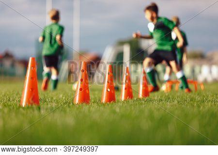 Football Slalom Drill Training Equipment. Row Of Red Training Cones. Boys Running Balls In The Backg