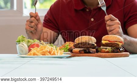 Young Man Holding Knife And Fork Are Ready To Eating A Hamburger, French Fries, And Spaghetti For Lu