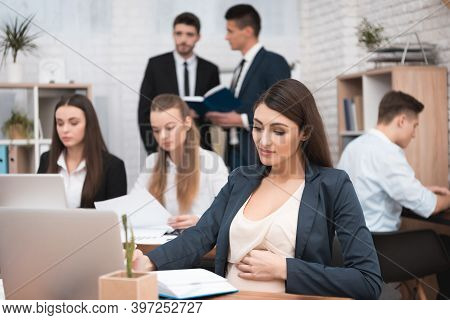 Attractive Pregnant Girl Is Working In Office With Colleagues. Pregnant Businesswoman In Workspace.