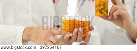 Doctors With Red Ribbon On Uniforms Are Holding Jars Of Medicines Closeup. Immunotherapy For Hiv Pos