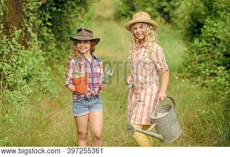 Agriculture Concept. Girls In Hats Planting Plants. Sisters Helping At Farm. Family Farm. Kids Havin