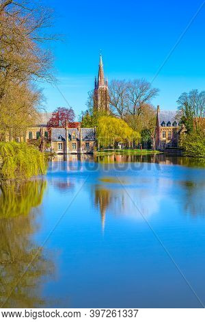 Minnewater Lake Panorama, Reflection Of Gothic Flemish Style House, Blue Sky, Spring Trees In Bruges