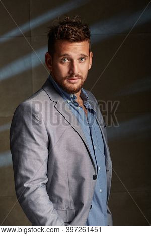 Portrait of good looking young caucasian businessman leaning against concrete wall wearing shirt and jacket.