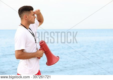 Handsome Male Lifeguard With Megaphone Near Sea