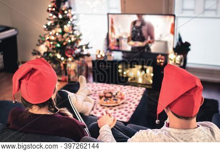 Couple Watching Tv On Christmas. Happy Family Holiday At Home. Man And Woman On Couch Relaxing With