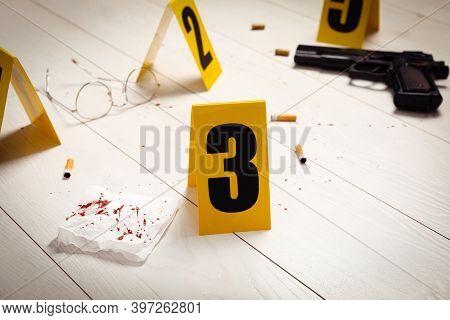 Evidences And Crime Scene Marker On White Wooden Table